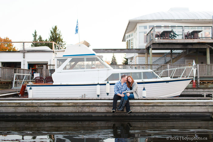happy-couple-sitting-in-front-of-boat