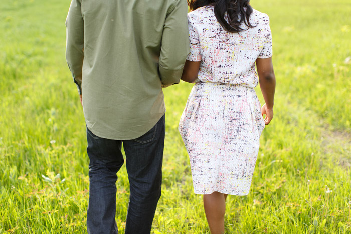 engaged couple walking in a field