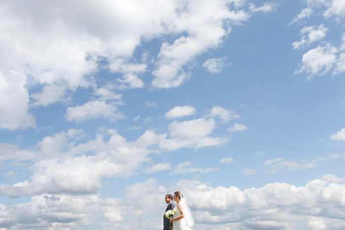 photo of a newly wedded couple walking in the sky